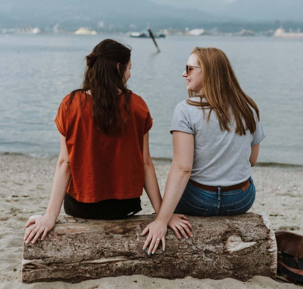 2 friends on beach offering each other affirmation