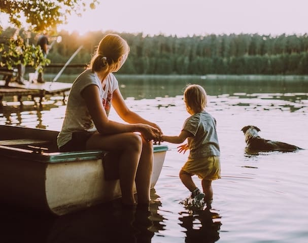 Mother reflects on financial freedom (with child and dog by water)
