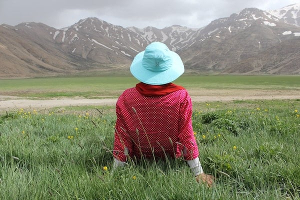Relax - Woman relaxing in meadow admiring mountains