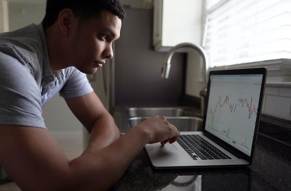 Young man checking his investment returns at home